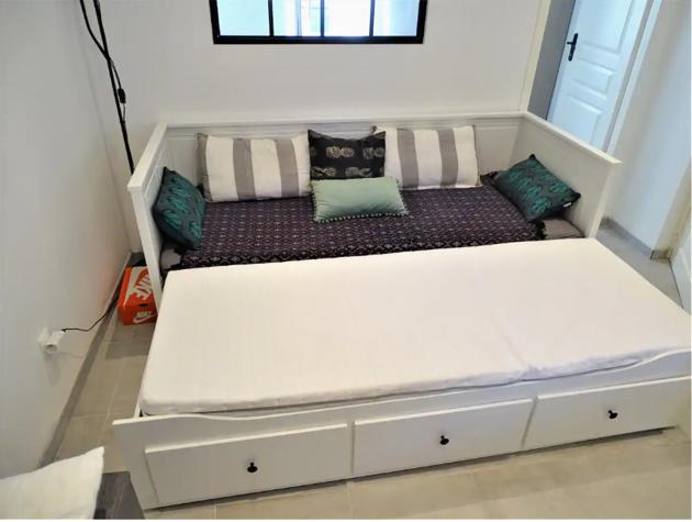 Le lit-gigone qui sert aussi de canapé pour augmenter le couchage dans cet appartement en location saisonnière et meublée.